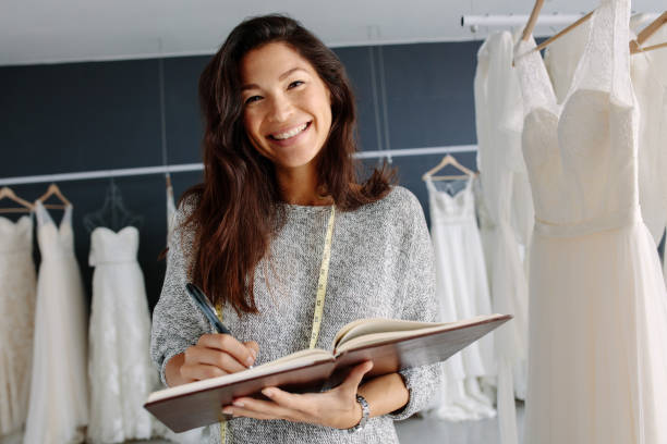 Asian woman tailor working in bridal boutique stock photo