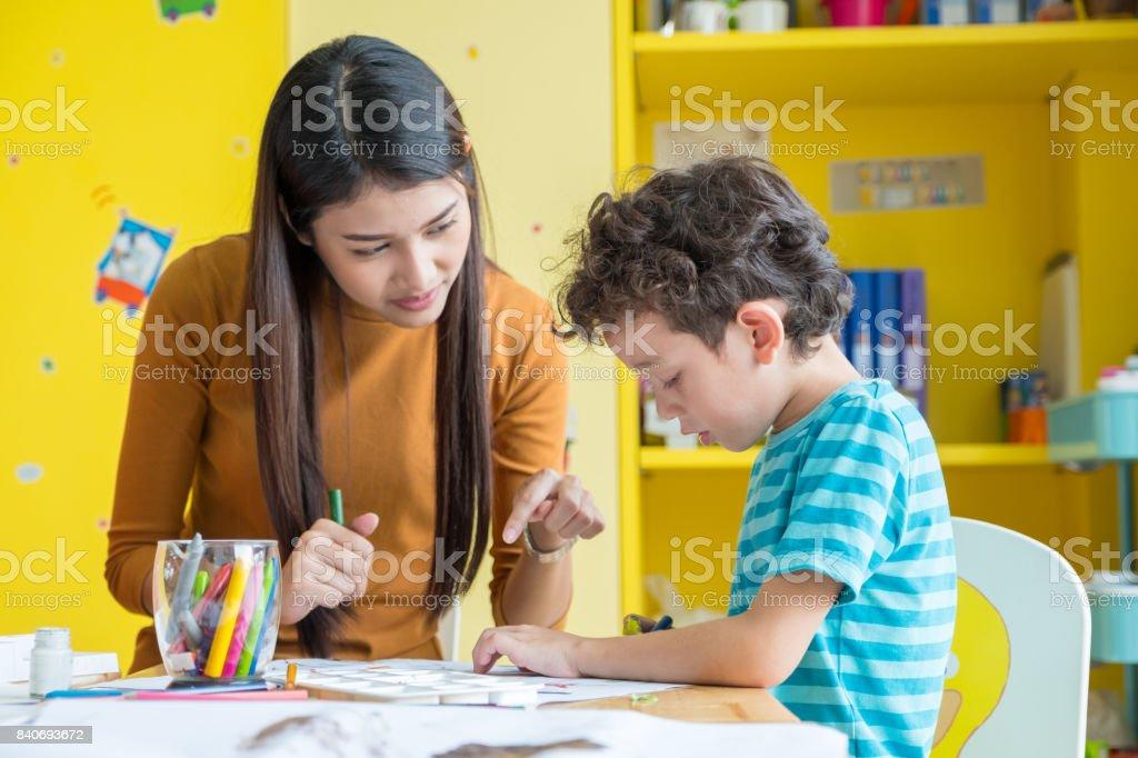 亞洲女教師教學男孩孩子塗色書放在幼稚園教育學校的教室裡的桌子上圖像檔