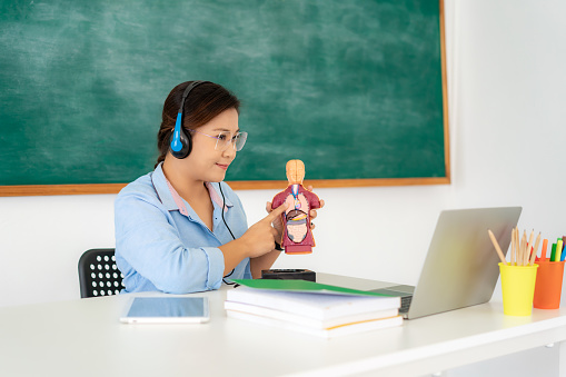istock Asian woman teacher teaching physiology science via video conference e-learning in laptop with blackboard at classroom. Homeschooling and distance learning ,online ,education and internet. 1243977786
