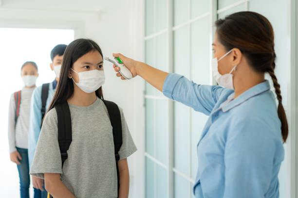 enseignante asiatique utilisant l'élève de contrôle de température de thermomètre pour la fièvre contre la propagation du covid-19 tandis que l'étudiant de retour à l'école, nouveau normal et concept d'éducation. - masque enfant photos et images de collection