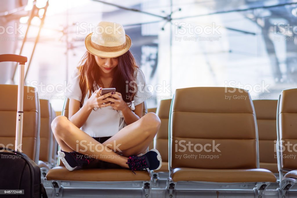 Asian woman teenager using smartphone at airport terminal sitting with luggage suitcase and backpack for travel in vacation summer relaxing waiting flight transport stock photo