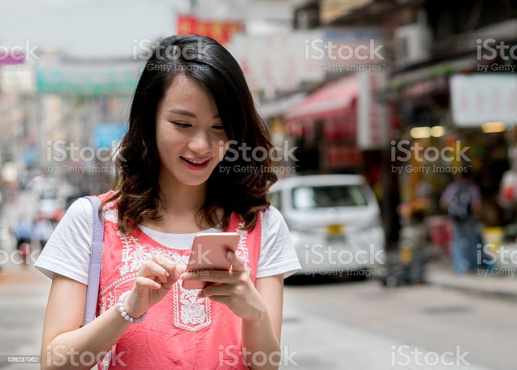 Asian woman text messaging in Hong Kong foto de stock libre de derechos