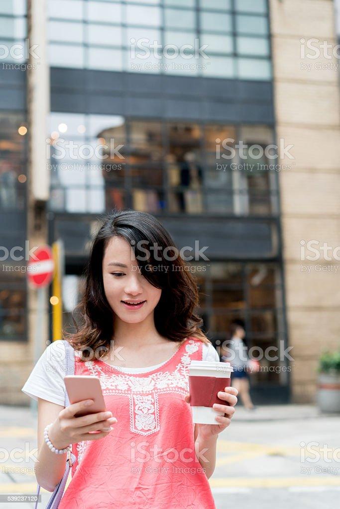 Asian woman texting and having coffee foto de stock libre de derechos