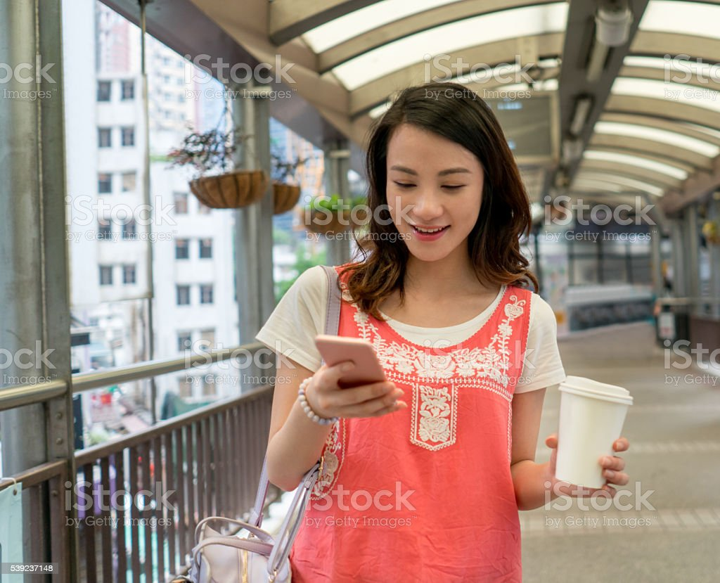 Asian woman texting and having coffee foto de stock libre de derechos