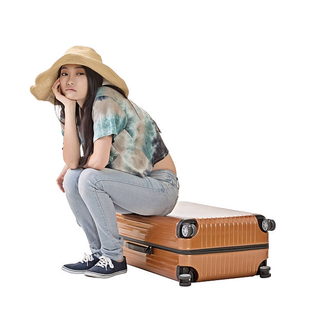Asian woman thinking and sitting on a luggage stock photo
