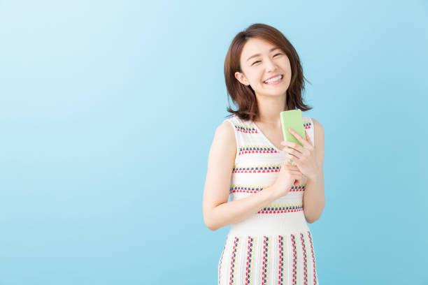 スマートフォンを見るアジアの女性 - 女性 ストックフォトと画像