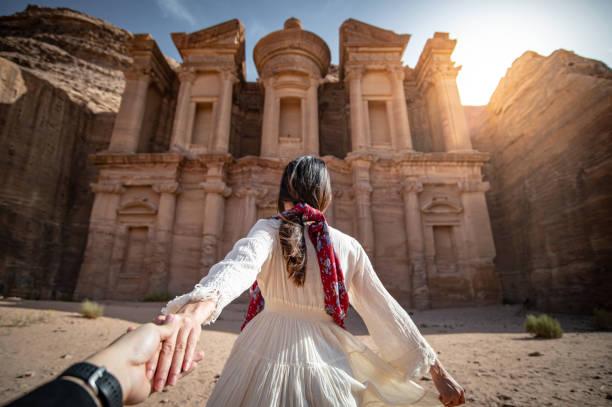 petra, ürdün'de asyalı kadın turist el ele tutuşuyor - beyaz elbise stok fotoğraflar ve resimler