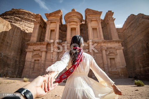 istock Asian woman tourist in white dress holding her couple hand at Ad Deir or El Deir, the monument carved out of rock in the ancient city of Petra, Jordan. Travel UNESCO World Heritage Site in Middle East 1139857487
