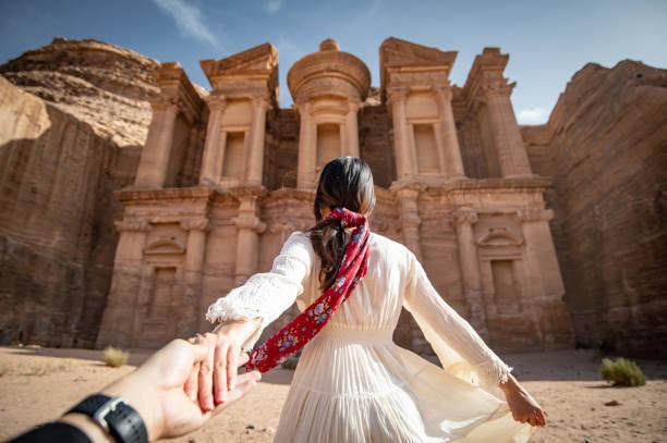 beyaz elbiseli asya kadın turist ad deir veya el deir, ürdün antik kentinde kaya oyulmuş anıt onu çift el tutarak. orta doğu 'da unesco dünya mirası bölgesi 'ne seyahat - beyaz elbise stok fotoğraflar ve resimler