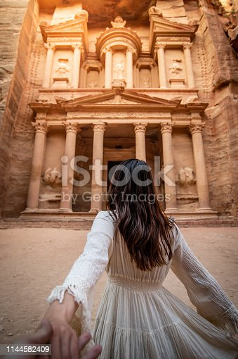 istock Asian woman tourist in white dress holding her couple hand at Treasury or Al-khazneh, the ancient city of Petra, Jordan. Travel UNESCO World Heritage Site in Middle East 1144582409