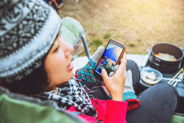Asian woman travel relax in the holiday. camping on the Mountain. Eating breakfast and sit play the phone. stock photo