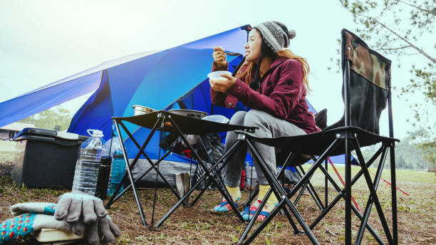 Asian woman travel relax in the holiday. camping on the Mountain. Eating breakfast stock photo