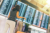 Asian woman traveler looking at flight information screen in an airport, holding suitcase, travel or time concept, warm light effect