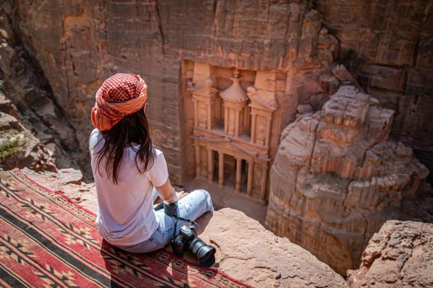 voyageur asiatique de femme s'asseyant dans petra, jordanie - jordan photos et images de collection