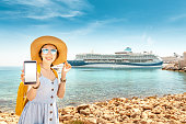 Asian woman traveler uses phone on the background of a large cruise liner. The concept of coverage, roaming and pay for the resort online