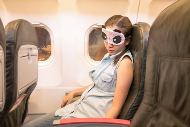 Asian woman traveller sleeping in the airplane Asian woman traveller sleeping in the airplane jet lag stock pictures, royalty-free photos & images