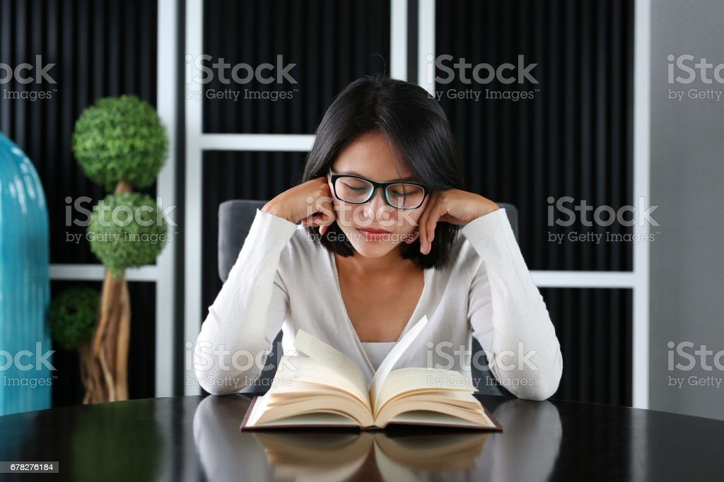 Asian woman under pressure reading a book in the library. stock photo