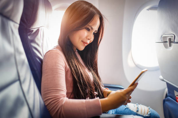 Asian woman use of mobile phone inside airplane stock photo