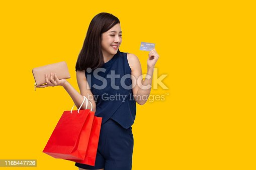 istock Asian woman using a credit card and enjoys shopping isolated on yellow background 1165447726