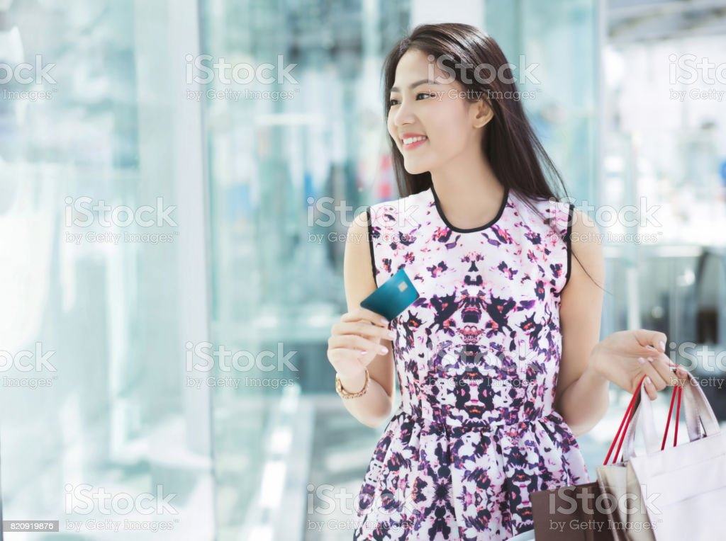Asian woman using credit card for shopping in the mall stock photo