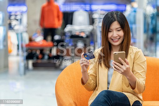 508915178istockphoto Asian woman using credit card with mobile phone for online shopping in department store over the clothes shop store background, technology money wallet and online payment concept, credit card mockup 1165996881