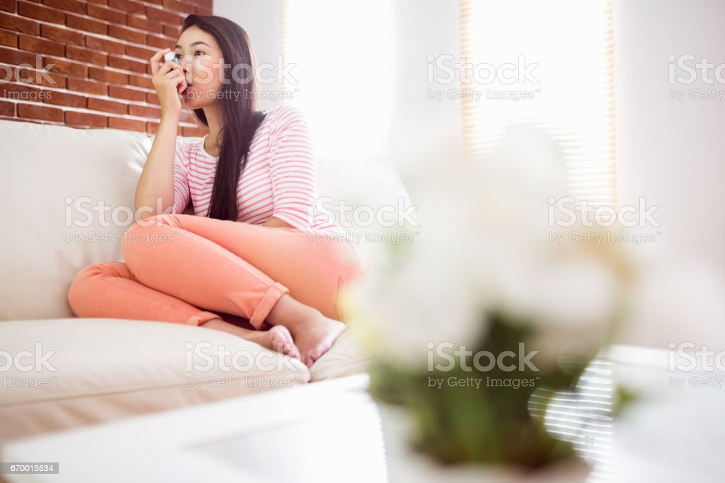 Asian woman using her inhaler on couch stock photo