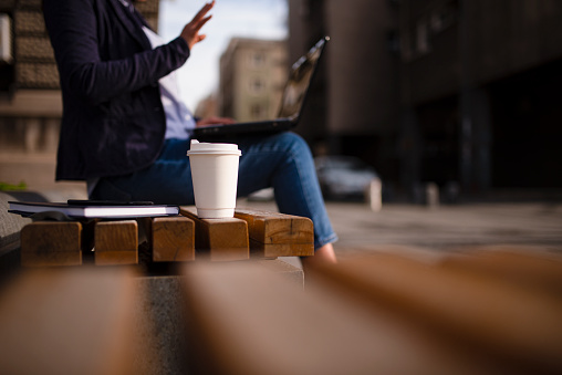 Asia,bench,outdoor,coffee cup,book,jeans,day,sun,springtime,autumn,business,women,green,lap top,break,freelance