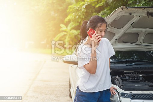 istock Asian woman using mobile phone and calling for help while the car broken down 1005356144