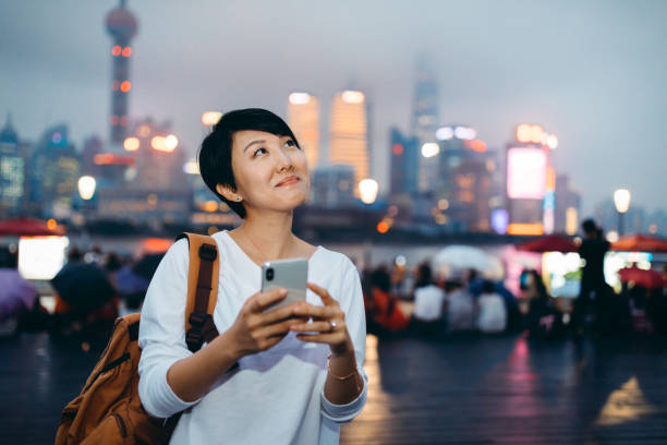 Asian woman using mobile phone in busy downtown, background is the financial skyscrapers in Lujiazui Financial District, Shanghai,China. stock photo