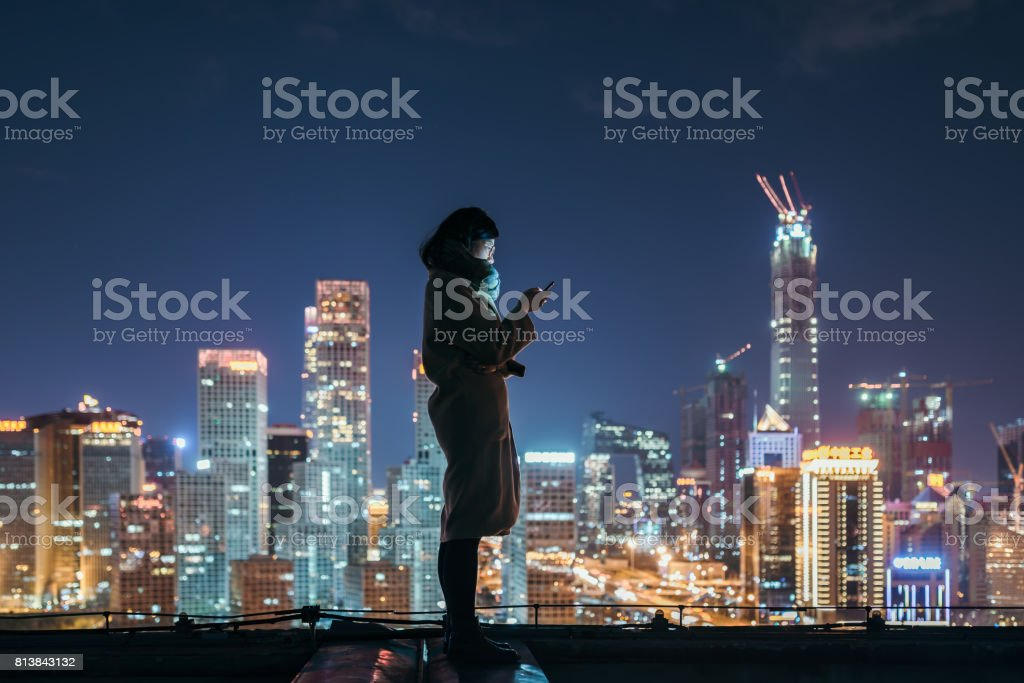 Asian Woman Using Mobile Phone In Downtown District stock photo