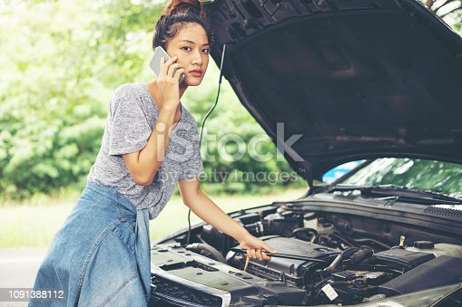860373412 istock photo Asian woman using mobile phone while looking and Stressed man sitting after a car breakdown on street 1091388112