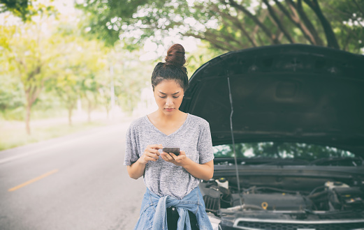 istock Asian woman using mobile phone while looking and Stressed man sitting after a car breakdown on street 860373412