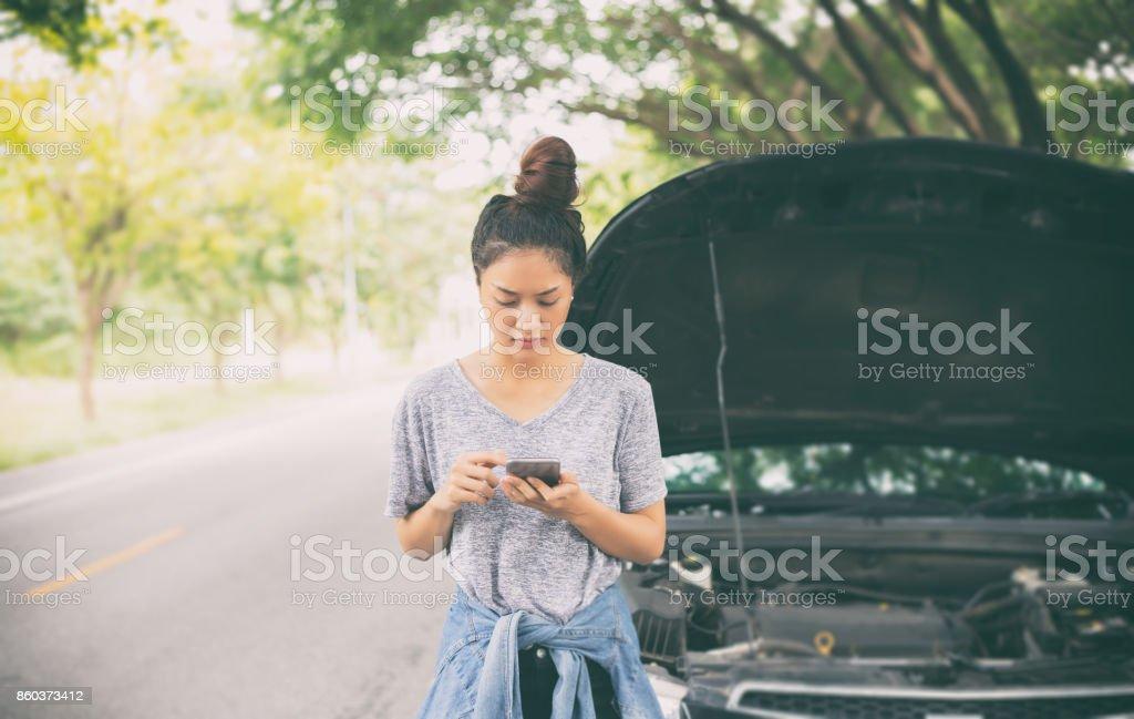 Aziatische vrouw met behulp van mobiele telefoon terwijl op zoek en gestresst man zit na een uitsplitsing van de auto op straat foto