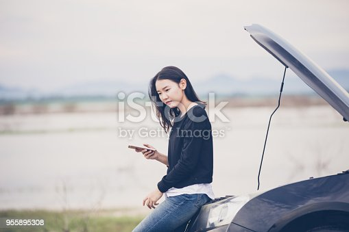 860373412 istock photo Asian woman using mobile phone while looking and Stressed man sitting after a car breakdown on street 955895308