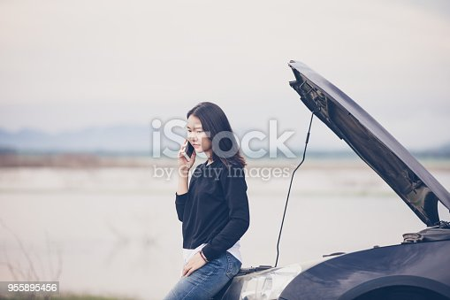 860373412 istock photo Asian woman using mobile phone while looking and Stressed man sitting after a car breakdown on street 955895456