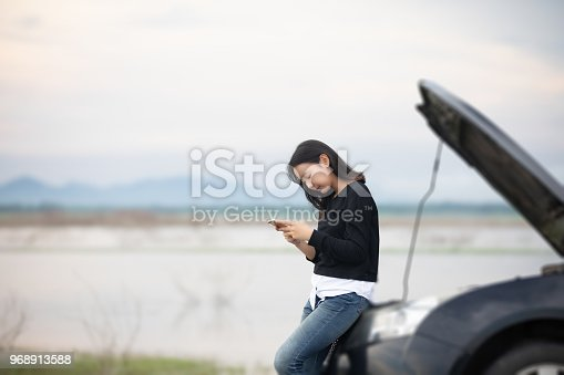 860373412 istock photo Asian woman using mobile phone while looking and Stressed man sitting after a car breakdown on street 968913588