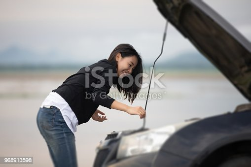 860373412 istock photo Asian woman using mobile phone while looking and Stressed man sitting after a car breakdown on street 968913598