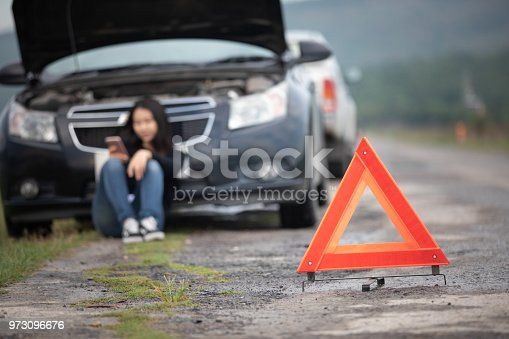 860373412 istock photo Asian woman using mobile phone while looking and Stressed man sitting after a car breakdown on street 973096676