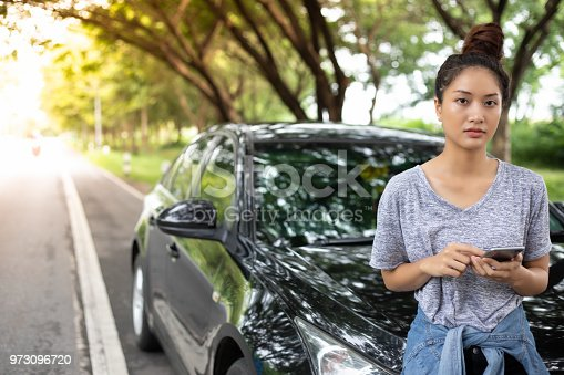 860373412 istock photo Asian woman using mobile phone while looking and Stressed man sitting after a car breakdown on street 973096720