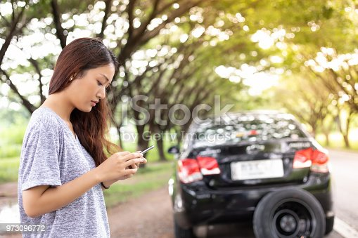 860373412 istock photo Asian woman using mobile phone while looking and Stressed man sitting after a car breakdown on street 973096772