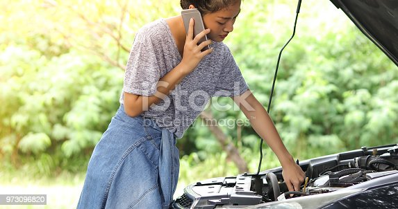 860373412 istock photo Asian woman using mobile phone while looking and Stressed man sitting after a car breakdown on street 973096820