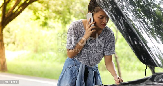 860373412 istock photo Asian woman using mobile phone while looking and Stressed man sitting after a car breakdown on street 973096830