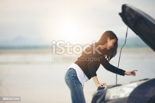 860373412 istock photo Asian woman using mobile phone while looking and Stressed man sitting after a car breakdown on street 995332340
