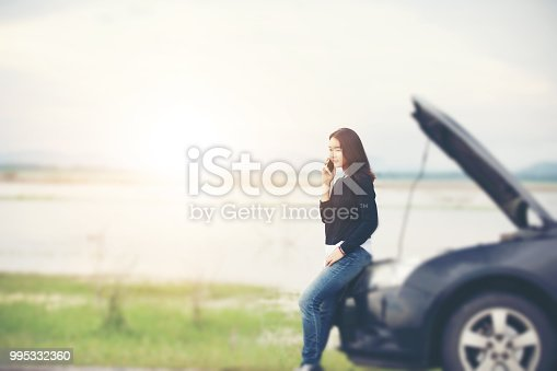 860373412 istock photo Asian woman using mobile phone while looking and Stressed man sitting after a car breakdown on street 995332360