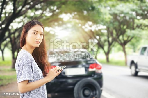 860373412 istock photo Asian woman using mobile phone while looking and Stressed man sitting after a car breakdown on street 995332374
