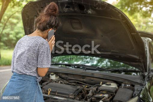 istock Asian woman using mobile phone while looking at broken down car on street 695207552