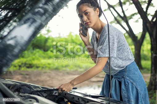 istock Asian woman using mobile phone while looking at broken down car on street 695207860