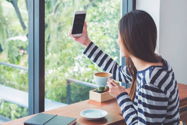 asian woman using on mobile phone live on social media while drinking coffee near window at cafe restaurant,digital age lifestyle,technolgy using concept. - woman chat video mobile phone foto e immagini stock