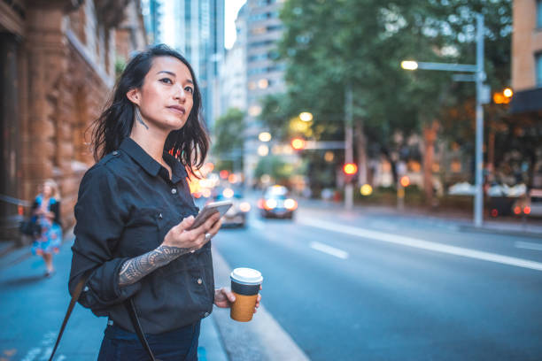 Asian woman using phone and waiting for taxi in Sydney stock photo