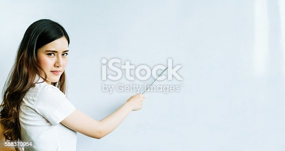 istock Asian woman using pointer on whiteboard, serious face, copy space 588370954